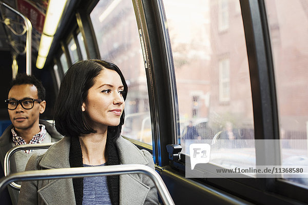 A young woman sitting on a train looking out of the window at an urban landscape  with a man sitting behind her looking away.