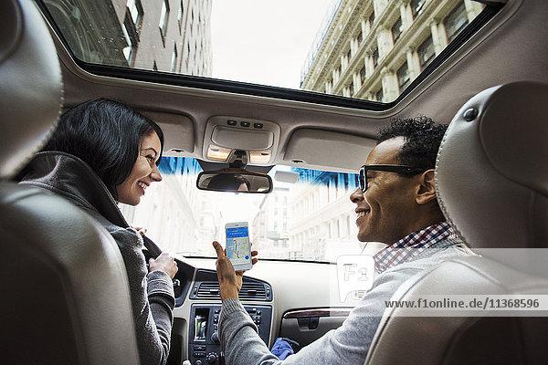Eine junge Frau und ein junger Mann in einem Auto  die vom Rücksitz aus eine Karte auf dem Display eines Mobiltelefons betrachten.