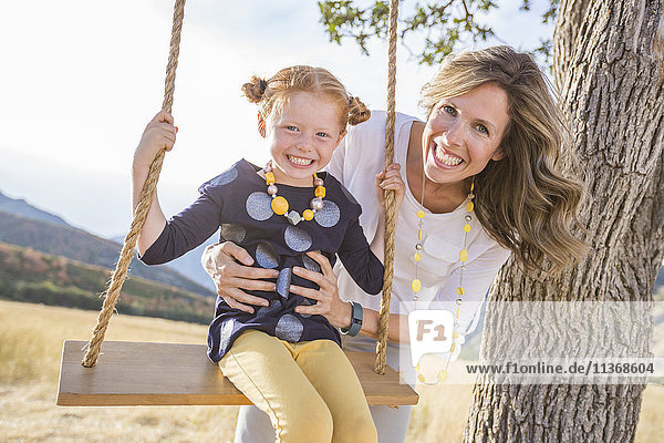 Mother with girl (4-5) sitting on swing