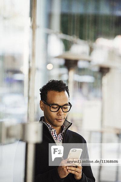 Ein junger Mann  der ein Handy in der Hand hält und lächelt.