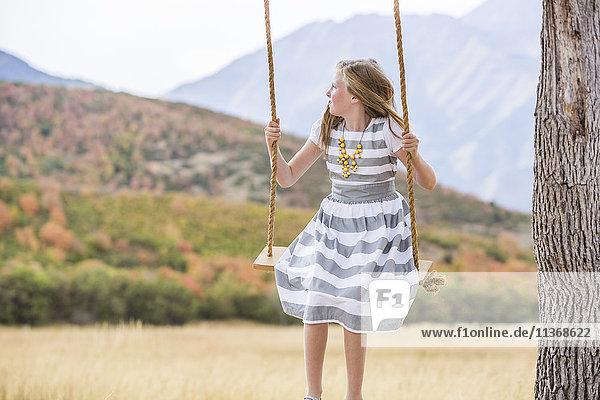 Girl (8-9) sitting on swing
