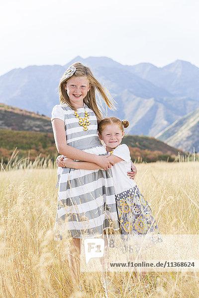 USA  Utah  Provo  Two girls (4-5  8-9) standing in field