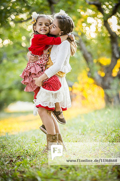 Girl holding and kissing sister in cherry orchard