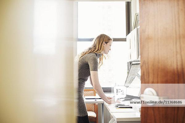 Eine Frau in einem Büro  gesehen durch eine offene Tür.