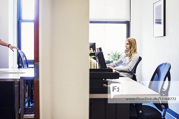 Eine Aufnahme der Tür zu zwei Büros  in einem Büro sitzt eine junge Frau an einem Schreibtisch  im anderen berührt ein Mann die Rückenlehne eines Schreibtischstuhls.