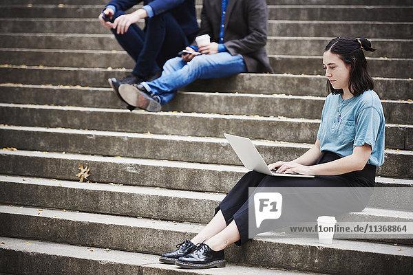 Eine junge Frau sitzt auf einer Freitreppe im Freien und arbeitet an einem Laptop  mit zwei Männern im Hintergrund.