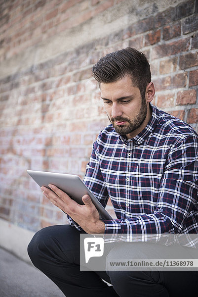 Young man using digital tablet and sitting against brick wall