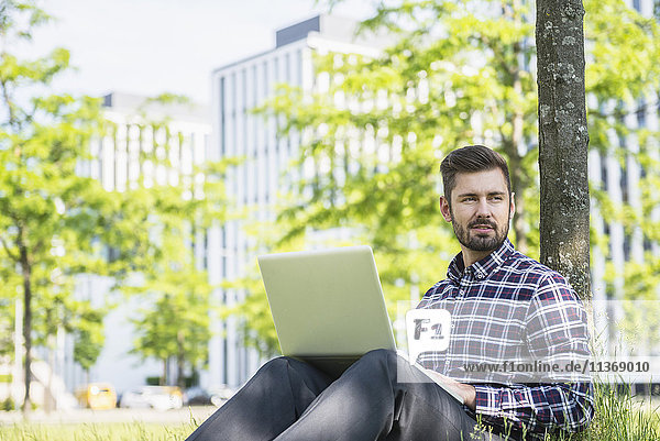Young man working on laptop and sitting in park