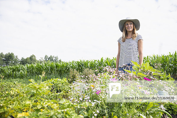 Mid adult woman standing with flowers in her community garden