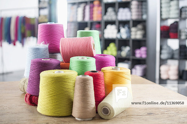 Group of multicolor reels of sewing thread on table