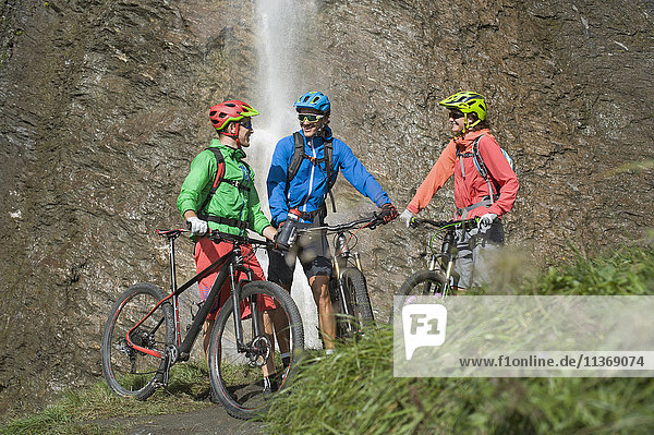 Three mountain biker friends standing in front of waterfall  Zillertal  Tyrol  Austria