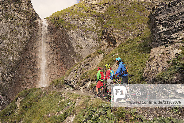 Three mountain biker friends watching waterfall  Zillertal  Tyrol  Austria