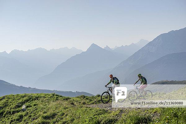 Two mountain biker friends riding on uphill,  Zillertal,  Tyrol,  Austria