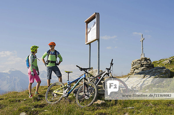 Young couple of mountain bikers watching information board on uphill  Zillertal  Tyrol  Austria