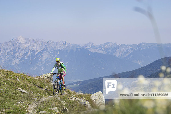 Mountain biker riding on uphill,  Zillertal,  Tyrol,  Austria