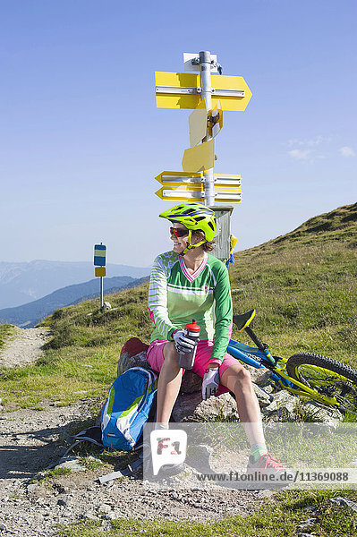 Mountain biker relaxing on hill and drinking water  Zillertal  Tyrol  Austria