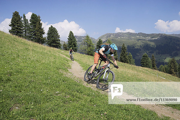 Two mountain bikers riding on downhill in alpine landscape  Zillertal  Tyrol  Austria