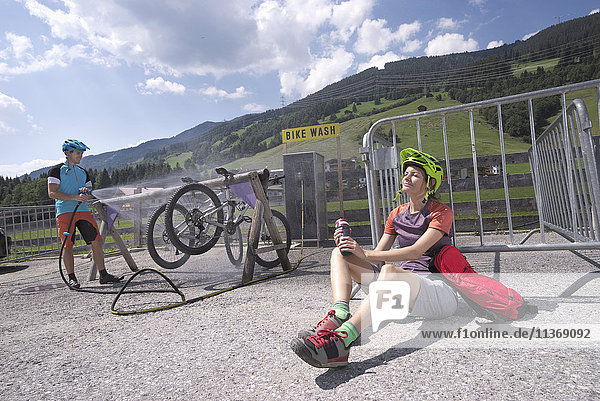 Mountain bikers relaxing after bike tour and her friend cleaning bicycles  Zillertal  Tyrol  Austria