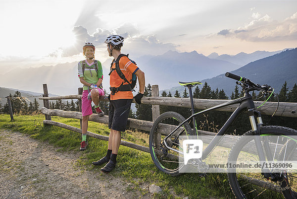 Young couple of mountain bikers standing by wooden fence during sunset  Zillertal  Tyrol  Austria
