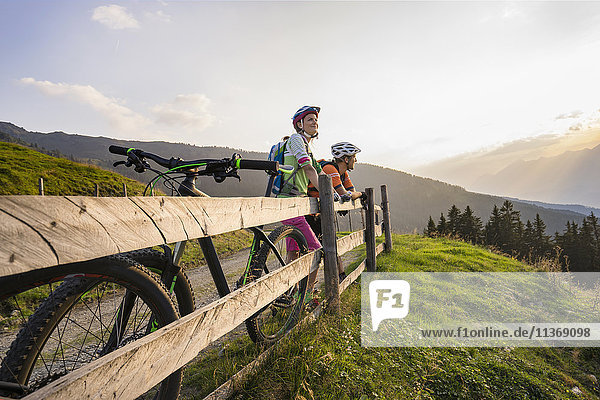 Young couple of mountain bikers standing by wooden fence looking at view during sunset  Zillertal  Tyrol  Austria