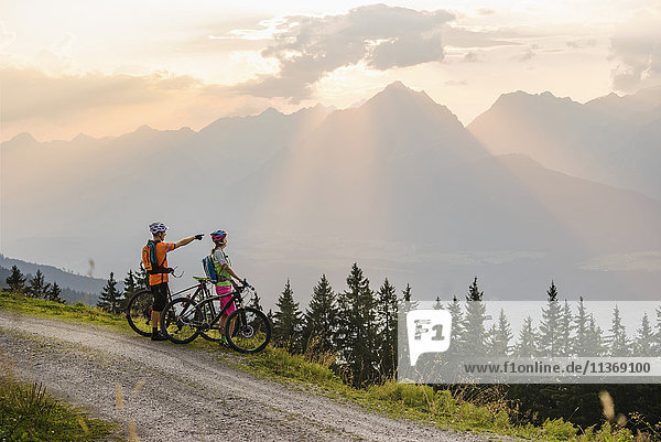 Young couple of mountain bikers standing on dirt road and looking at view during sunset  Zillertal  Tyrol  Austria