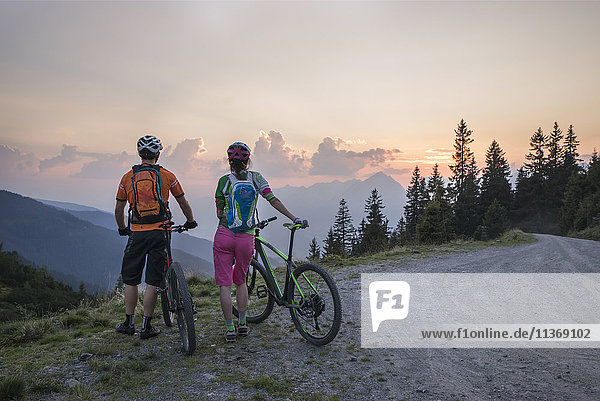 Rear view of young couple of mountain bikers standing in the alpine landscape and looking at view during sunset  Zillertal  Tyrol  Austria