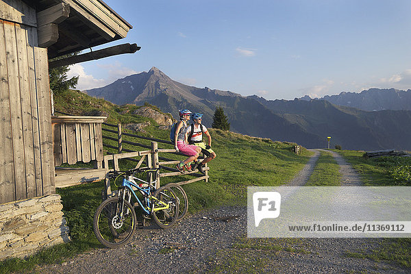 Young couple of mountain bikers sitting on wooden fence  Zillertal  Tyrol  Austria