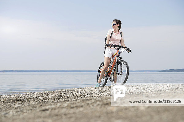Mature woman with bicycle at lakeshore