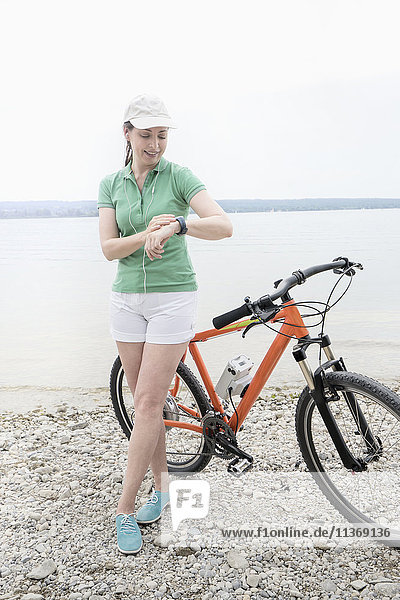 Mature woman with electric bike by lake checking the time Mature woman with electric bike by lake checking the time