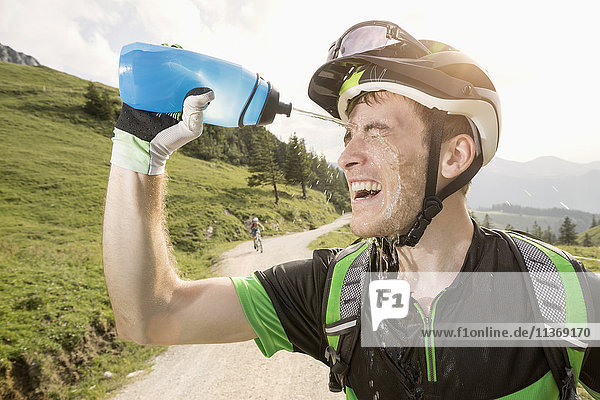 Mountain biker pouring water on his face  Kampenwand