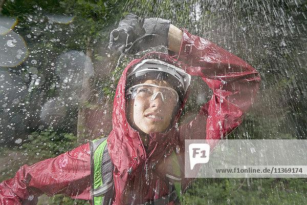Mountainbiker standing in rain with hand over head  Kampenwand