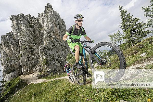 Mountain bikers cycling uphill in nature  Kampenwand