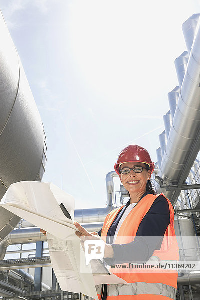 Female engineer smiling with blueprint at geothermal power station