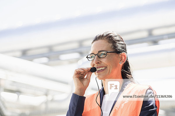 Female engineer wearing headset and smiling at geothermal power station Female engineer wearing headset and smiling at geothermal power station