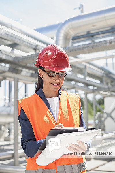 Female engineer writing in document at geothermal power station Female engineer writing in document at geothermal power station