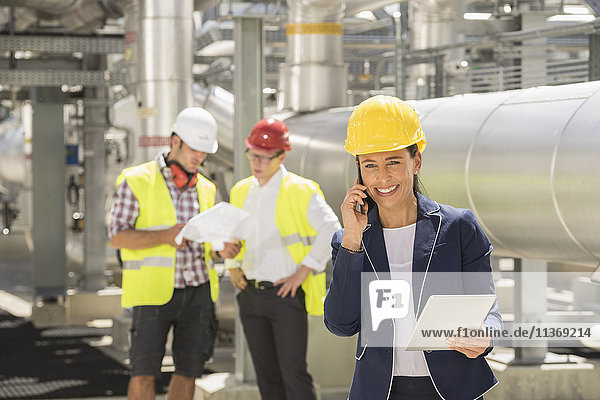 Female engineer talking on mobile phone with her colleague discussing in background