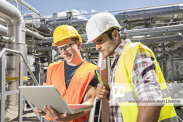 Engineer with his colleague in meeting with laptop at geothermal power station