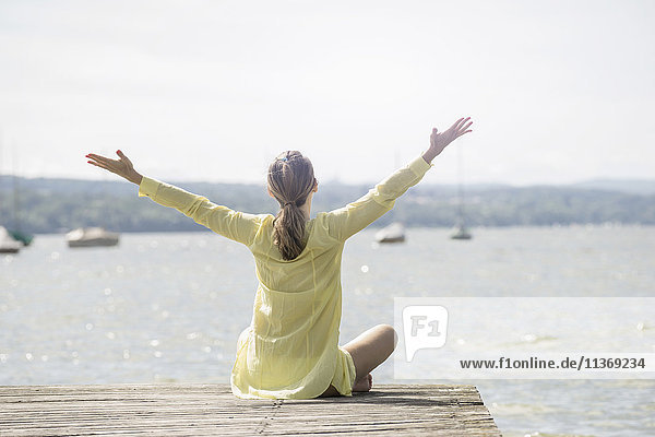 Rear view of a woman with arms raised sitting on boardwalk at the lake  Ammersee  Upper Bavaria  Germany