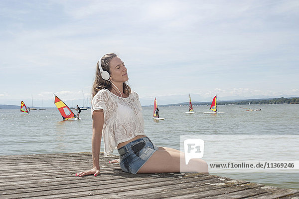 Woman listening to music and sitting on boardwalk at the lake  Ammersee  Upper Bavaria  Germany