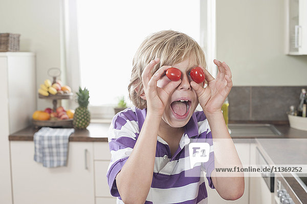 Playful boy making face with tomatoes