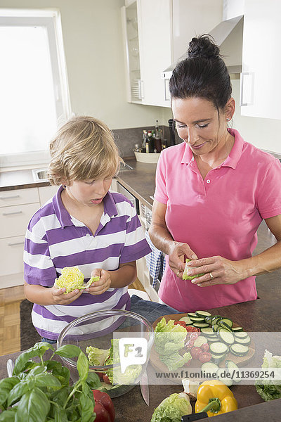 Woman with her son chopping vegetables in kitchen