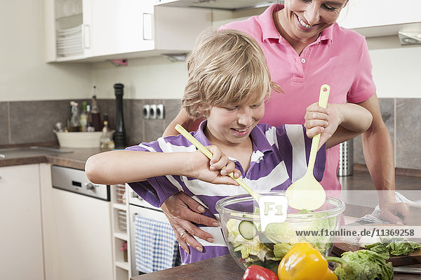 Woman with her son preparing salad in kitchen
