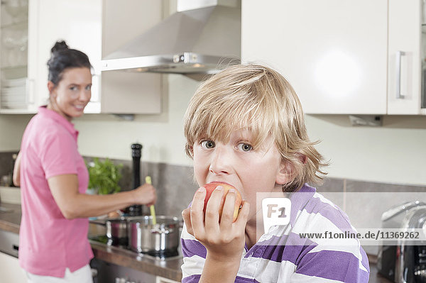 Boy eating an apple in kitchen
