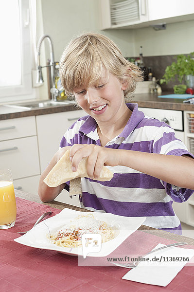Boy grating cheese over spaghetti