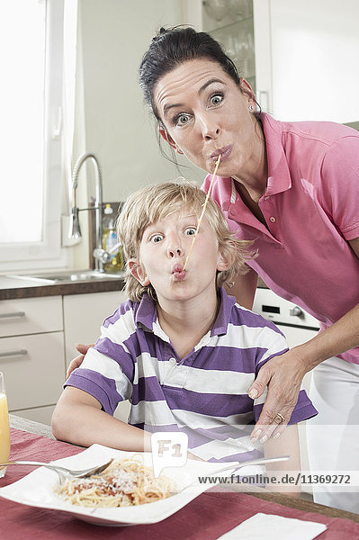 Portrait of a woman with her son eating spaghetti in funny way