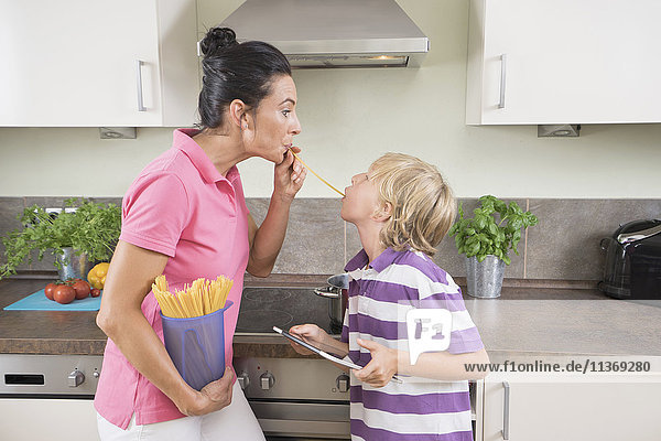 Woman with her son playing with Spaghetti in kitchen