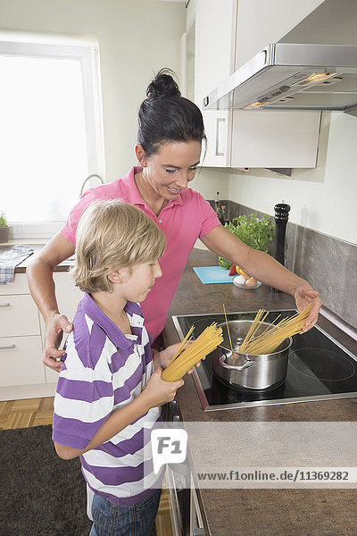 Woman with her son cooking spaghetti together