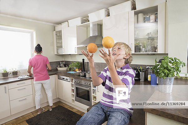 Boy juggling with oranges while mother preparing food