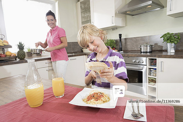 Boy grating cheese over spaghetti while his mother cooking food