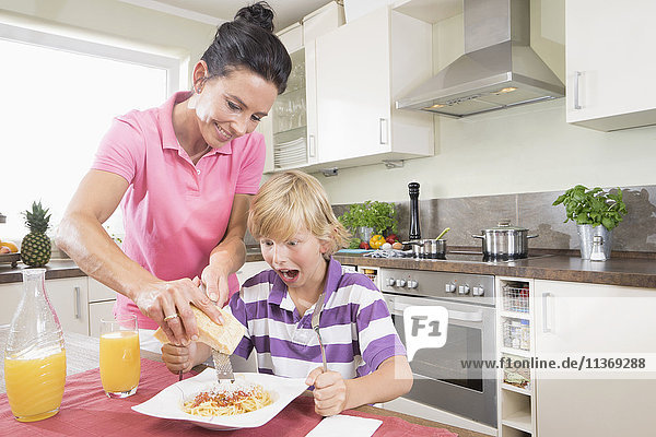 Woman grating spaghetti on son pasta
